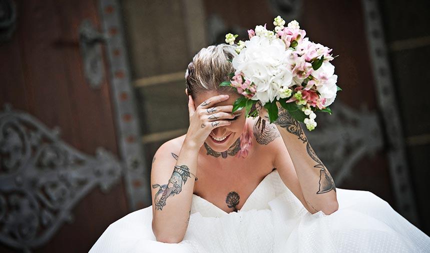 Braut sitzt auf im Brautkleid und Blumenstrauß in der Hand. Hält Hand vor Gesicht und lacht.